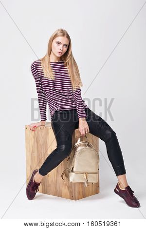 Pretty young girl in sweater striped posing in the studio. Beauty fashion photos. Model sitting on wood box white background