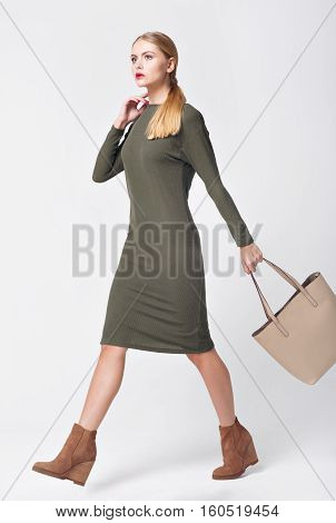beauty, fashion and happy people concept - young woman in green dress and high heels. It comes with bag.