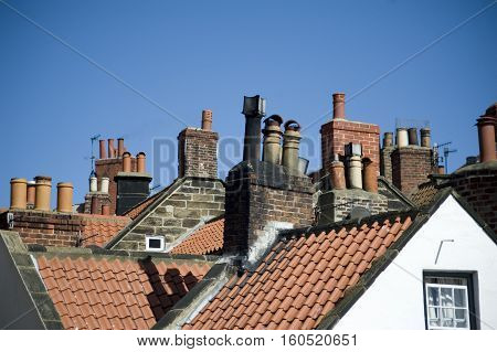 Rooftop view of a variety of different chimney pots on quaint cottages in the fishing village of Robin Hoods Bay UK