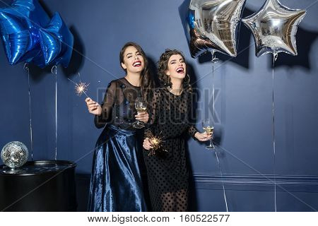 Two laughing models in trendy night dresses with glasses and sparklers in the hands on the blue wall background in the studio. There are blue and silver star-balloons, black barrel with disco ball.