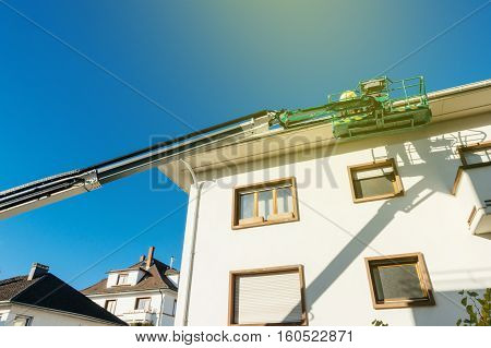 View from below to the modern hydraulic mobile construction platform elevated on the last floor of a house with construction worker preparing to to work