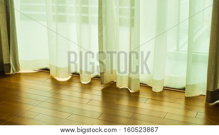 Transparent curtain sliding door in the room with the light shining through the curtains background.