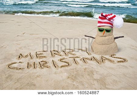 Christmas snowman on beach with sunglasses and Merry Christmas written in sand