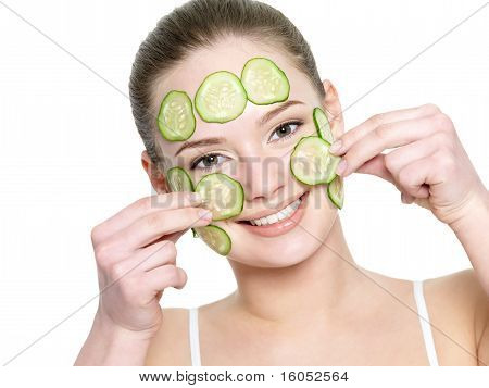 Happy Girl Applying Facial Mask Of Cucumber