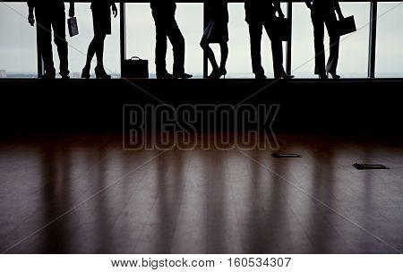 Legs of business people against window in dark shapes