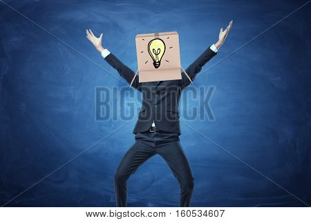 Businessman standing with cardboard box on his head with a drawn electric bulb on blue blackboard background. Brainstorming. Business development. Solving problems. Anonymous person.