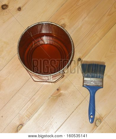 varnish brush with tin can on wooden floor