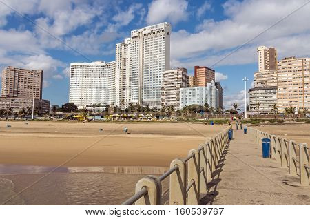 DURBAN SOUTH AFRICA - DECEMBER 2 2016: Many unknown people and concrete pier leading toward golden Mile blue cloudy city skyline in Durban South Africa