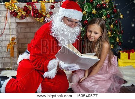 Santa Claus and a girl in a dress. Christmas Scenes. Kid reading a book with Santa
