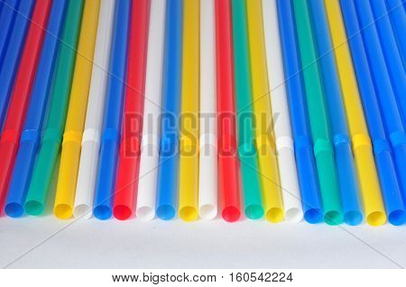 multi-colored tubules for cocktail are put in a row on a white background