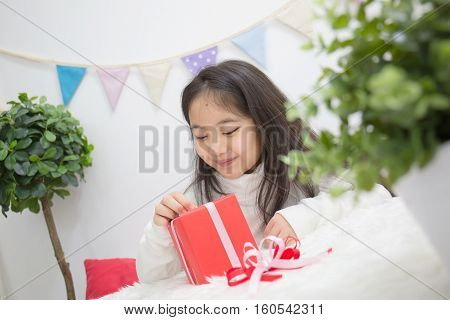 Happy Asian girl opening a present to guess whats inside