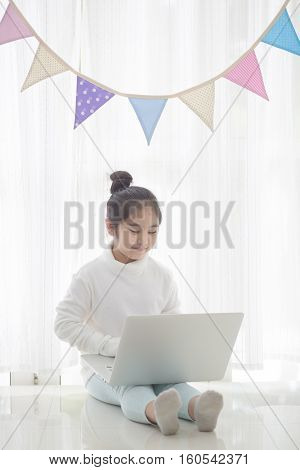 Happy Asian girl using laptop in decorated room with pastel triangle party flag, High key process