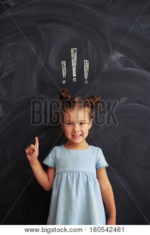 Pretty little girl in a casual dress with two buns is smiling and holding finger up against chalk drawing of three exclamation marks