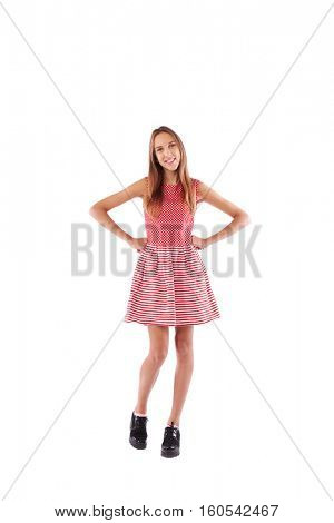 Full-length skinny girl with hands on hips standing over white background. Wearing cute dress in white and red colors with black shoes