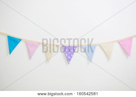 Colorful Party flags bunting hanging on white wall for holiday decoration