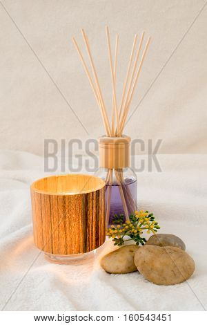 A bottle of purple scented oil along with a tealight and stones on a fluffy background