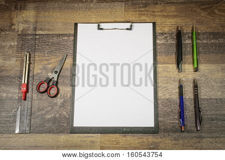 On a subsoil of wood are clear arranged a clamp board with a white sheet of paper 4 ballpoint pens a ruler a circle and scissors