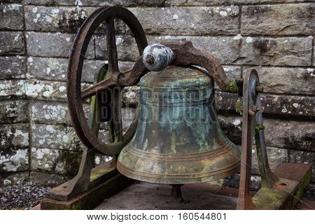 An old rusty disused church bell located in front of an old church