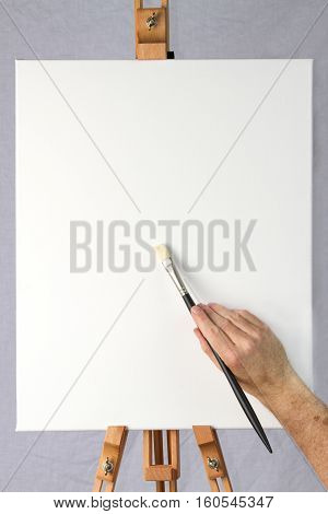 Close-up of artist starting to paint on a blank canvas on an easel ready for adding your own image or text or design