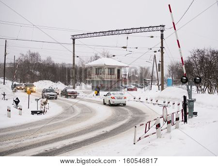 Petrozavodsk, Russia - January 15, 2016: Cars driving on a winter road across the railway crossing
