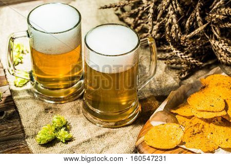 Two beer mugs with hops and chips and wheat on wooden table