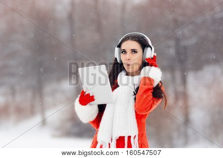 Surprised Winter Girl with Headphones and PC Tablet