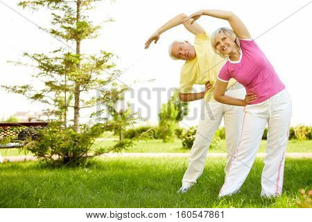Two senior people bending over outdoors in nature