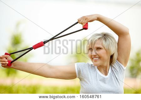 Portrait of a mature woman training with resistance band