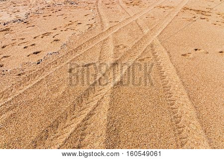 Close uo of two vehicles tire tracks crossing over leaving patterns on beach sands textured background