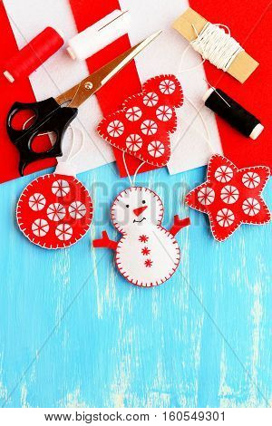 Cute Christmas tree embellishment. Felt snowman, Christmas tree, star and ball embellishment, materials and tools for sewing on wood background with copy space for text. Christmas kids DIY background