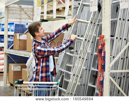 Man Chooses A Construction Ladder In Shop