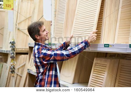 Man Chooses Wooden Facades For Furniture In Store