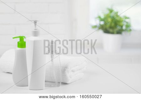 White towel and cosmetic dispensers on abstract bathroom window background