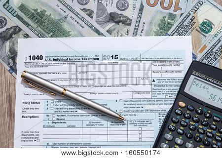 federal income tax return 1040 documents with pen calculator dollars