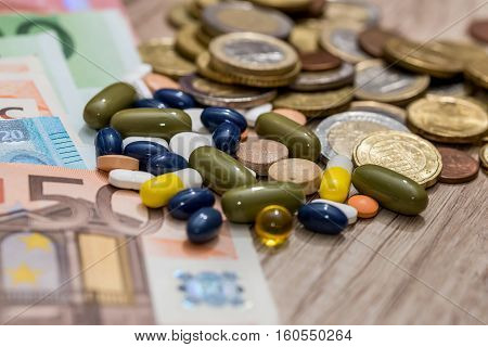 euro banknote and coin with drug on desk