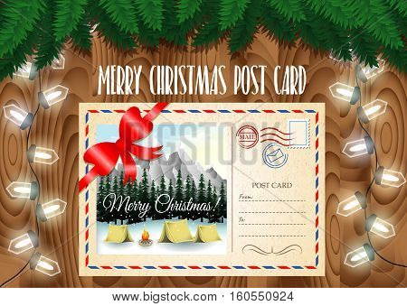 Merry Christmas post card design on the wood table with Christmas tree branches and garland lights. Camping in mountains landscape.