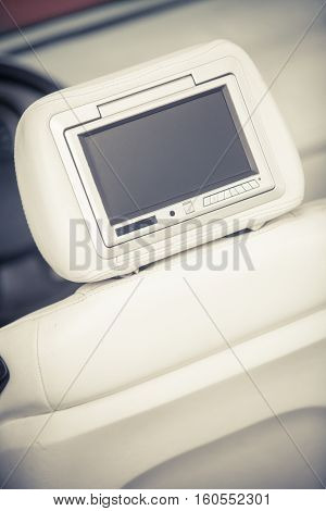 Close up shot of a small screen dvd player inside a car.
