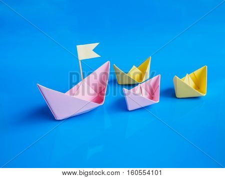 Leadership and team work concept Craft of paper boat (Origami boat) on blue background