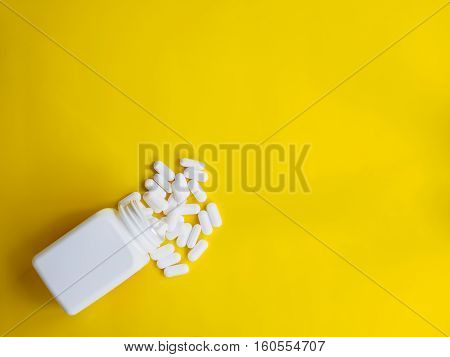 white pills spill out white bottle on yellow background with copy space