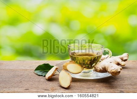 Ginger tea cup with ginger root slice of hot drink asian style on wooden table natural background