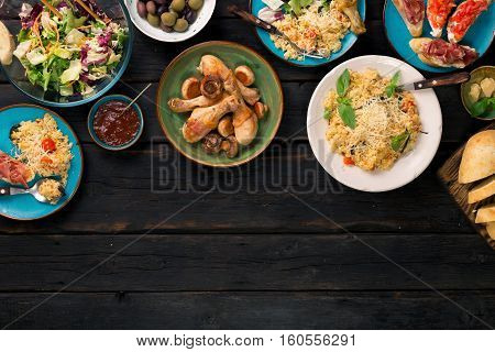 Risotto with cherry tomatoes basil and parmesan cheese roasted chicken legs and snacks on a dark wooden table with copy space. Italian food table top view