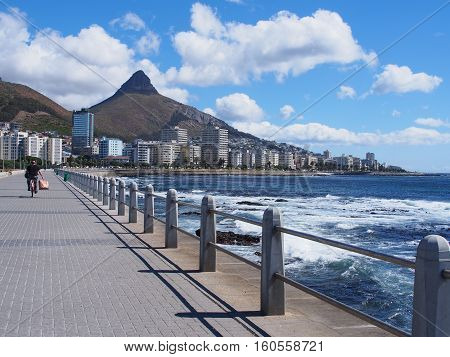 A man is cycling on the road beside the sea at Camps Bay, South Africa. Lion's Head mountain on the background.