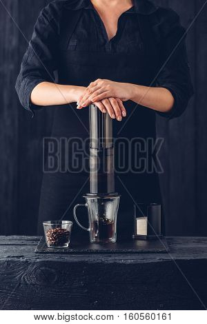 Professional barista preparing coffee alternative method on black background