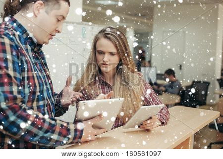 business office winter christmas people concept- Business partners discussing documents and ideas standing in front of his office. over snow background