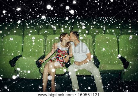 love winter christmas people concept- Stylish couple having romatic moment in a movie theater over snow background