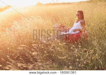 Trendy woman in casual clothes working on laptop outdoos. Freedom and freelancing concept