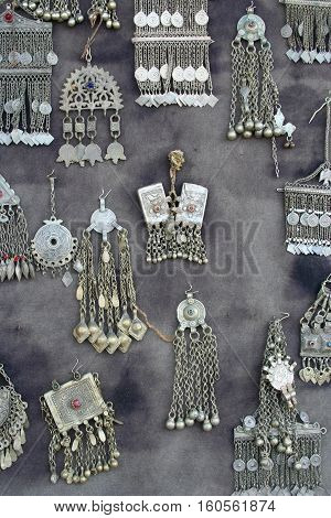 antique silver jewellery on grey color fabric background