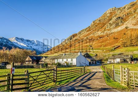 Typical whitewashed farm house and barn with track leading to it at Langdale in the English Lake District, Cumbria. Snow covered fell beyond, background of cloudless blue sky.