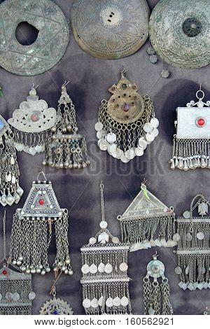 antique silver jewelry on grey color fabric background