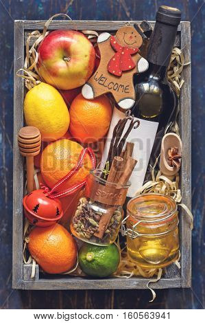 Mulled wine kit with bottle of wine, fruits and spices.